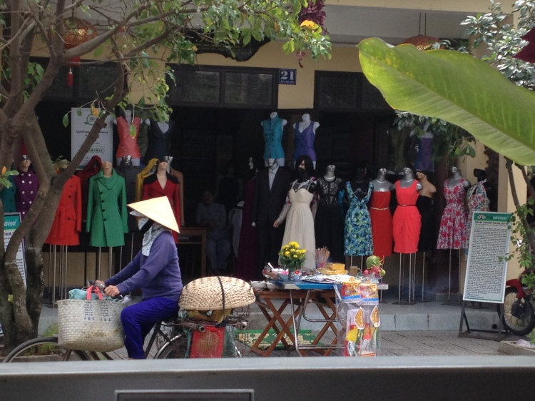 Quintessential Hoi An: Conical hats, bikes, and offerings in front of tailor shops.
